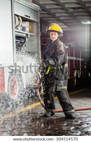 Portrait of confident young firewoman spraying water during practice at fire station - stock photo