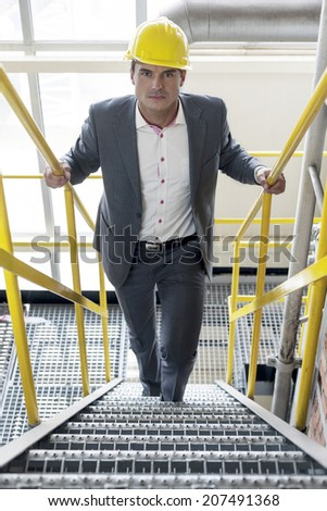 Portrait of confident young male architect walking up stairs in industry