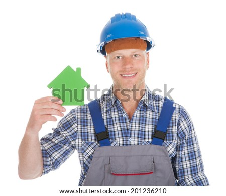 Portrait of confident young male builder holding green house model over white background - stock photo