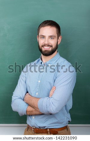 Portrait of confident young male professor with arms crossed standing against chalkboard