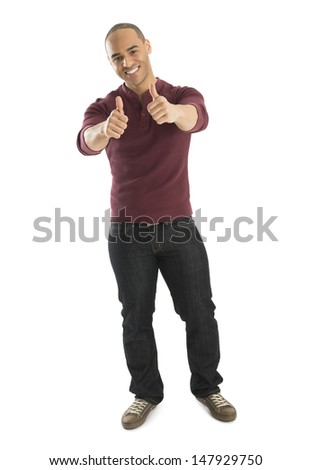 Portrait of confident young man gesturing thumbs up against over white background - stock photo