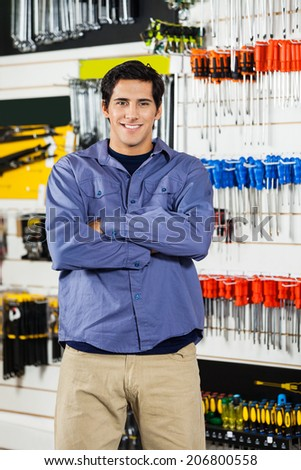 Portrait of confident young man standing arms crossed in hardware shop