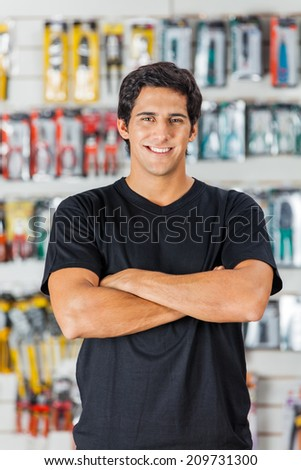 Portrait of confident young man standing arms crossed in hardware store