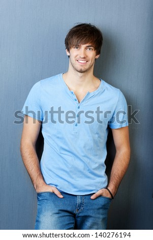 Portrait of confident young man with hands in pocket standing against blue wall