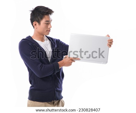 Portrait of confident young man with laptop standing