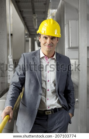 Portrait of confident young manager wearing hard hat in industry - stock photo