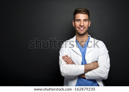 Portrait of confident young medical doctor on dark background - stock photo