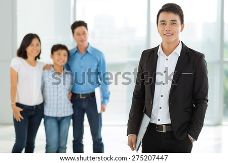 Portrait of confident young real estate broker and happy family in the background