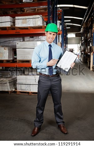 Portrait of confident young supervisor displaying clipboard standing at warehouse - stock photo