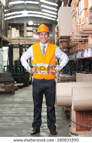 Portrait of confident young supervisor standing at warehouse - stock photo