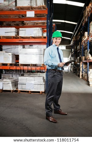Portrait of confident young supervisor with clipboard standing at warehouse - stock photo