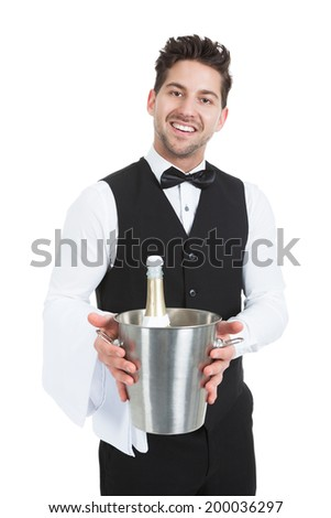 Portrait of confident young waiter holding ice bucket with champagne bottle over white background