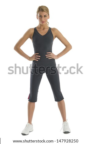 Portrait of confident young woman in sports clothing with hands on hips standing against white background - stock photo