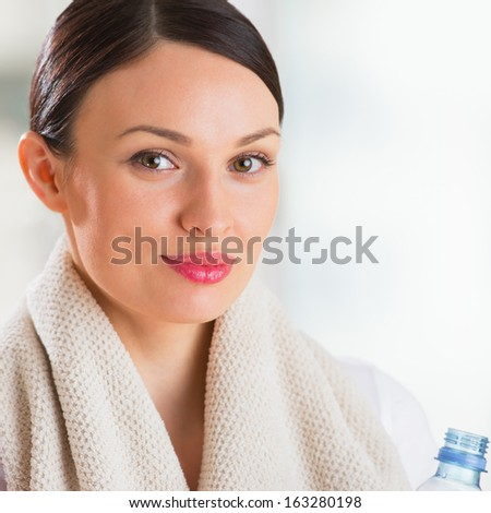 Portrait of confident young woman in sportswear holding a water bottle in gym - stock photo
