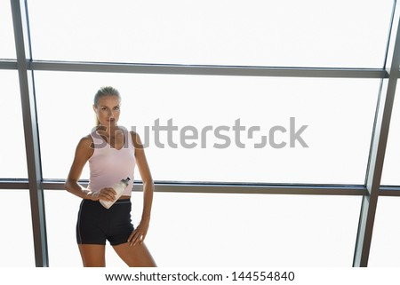 Portrait of confident young woman in sportswear holding water bottle in gym