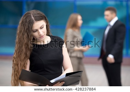 Portrait of confident young woman looking through documents with serious facial expression outdoors. Successful beautiful woman posing on the street in summer with businesspeople on the background - stock photo