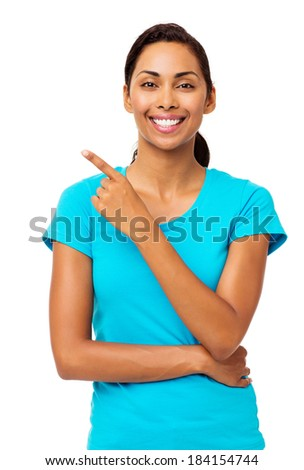 Portrait of confident young woman pointing sideways against white background. Vertical shot. - stock photo