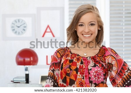 Portrait of confident young woman smiling, looking at camera. - stock photo