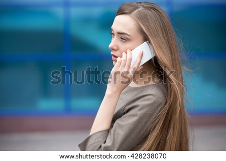 Portrait of confident young woman talking on smartphone outdoors. Serious beautiful caucasian woman using mobile phone, making call on the street in summer. Copy space - stock photo