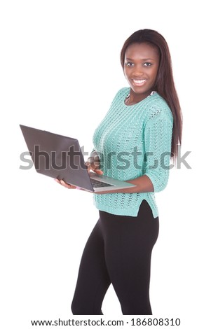 Portrait of confident young woman using laptop over white background - stock photo