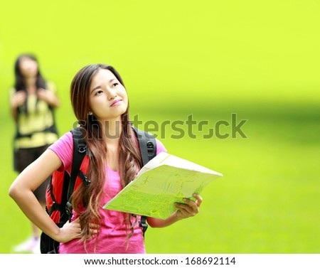 portrait of confuse asian girl camping in the park holding a map - stock photo