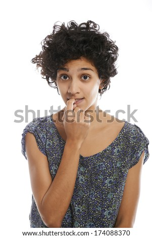 Portrait of confused and uncertain hispanic woman biting nail on white background and looking at camera - stock photo