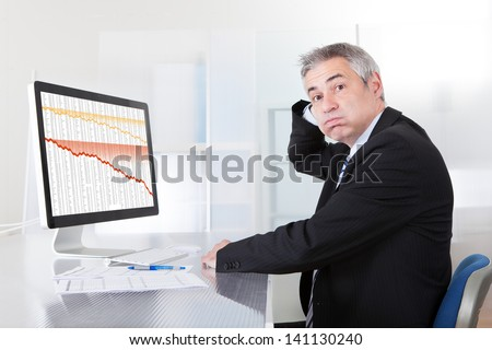 Portrait Of Confused Businessman With Computer In Office - stock photo