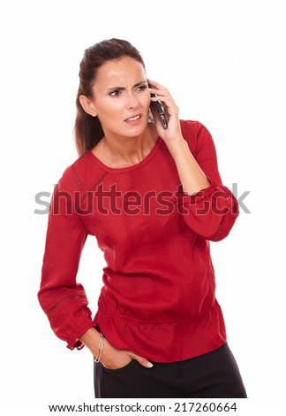 Portrait of confused hispanic lady on red blouse talking on her phone while looking to her left and standing on isolated white background - copyspace - stock photo