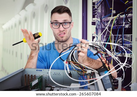 Portrait of confused it professional with screw driver and cables in front of open cpu against data center - stock photo