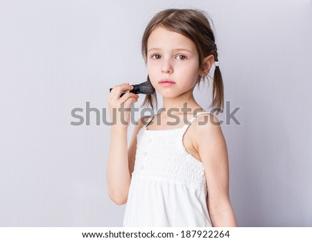 Portrait of confused preschooler girl with brush makeup  at home - stock photo