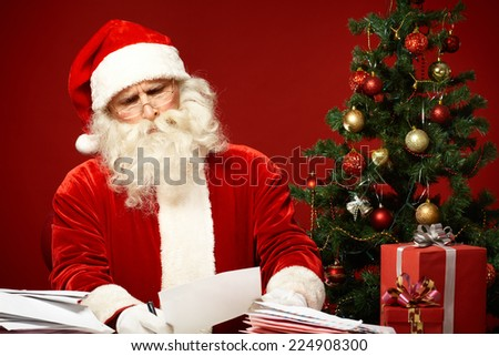 Portrait of confused Santa Claus reading letter - stock photo