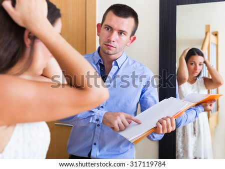 Portrait of confused tenant and furious landlord with a unpaid bills indoors  - stock photo