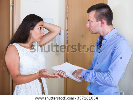 Portrait of confused tenant and furious landlord with unpaid bills in home   - stock photo