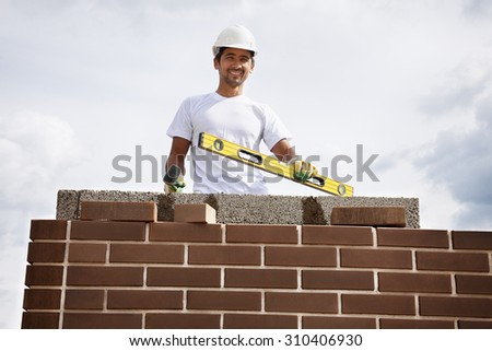 Portrait of construction bricklayer worker against sky.   - stock photo