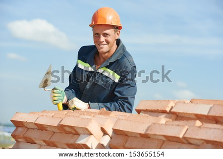 Portrait of construction mason worker bricklayer with trowel putty knife outdoors at building area - stock photo