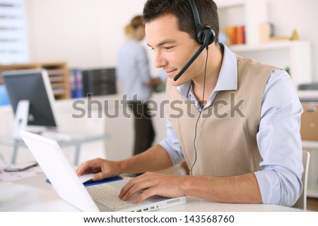 Portrait of consultant on the phone with headset - stock photo
