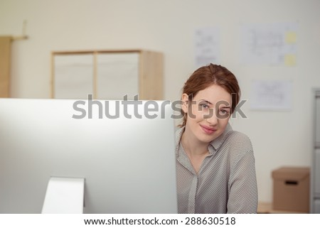 Portrait of Contented Young Woman with Red Hair Peeking Around Computer Monitor and Sitting at Desk in Relaxed Casual Office - stock photo