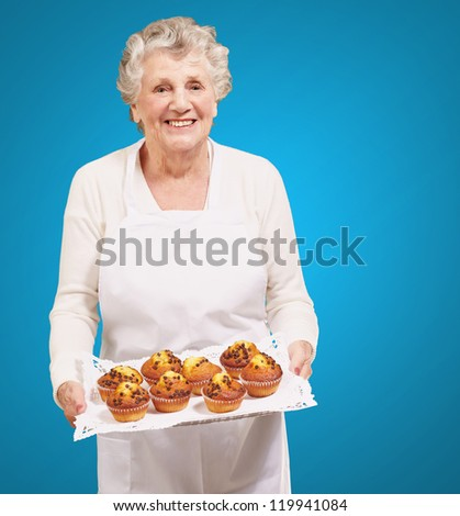 portrait of cook senior woman holding a chocolate muffins tray over blue background - stock photo