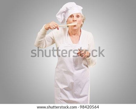 portrait of cook senior woman with a wooden spoon covering her mouth over a grey background - stock photo