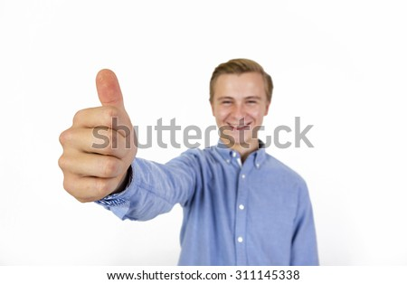 portrait of cool boy with blue shirt showing thumbs up sign  in studio, focus on thumbs up not at face - stock photo