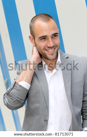 Portrait of cool businessman standing in town - stock photo