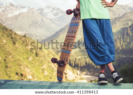 Portrait of cool, funny handsome man with skateboard outdoor at mountain. Skatebord at mauntain. Real guy with strong character and personality. Hipy