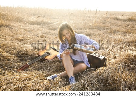 Portrait of Country hippie girl with acoustic guitar at wheat field drink pour black coffee or green tea from metal mug thermos of relying on old retro vintage aged suitcase against summer background - stock photo