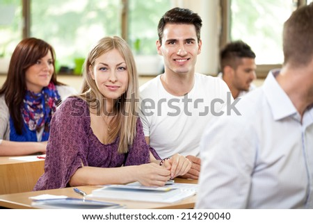 Portrait of couple cheerful students in classroom - stock photo