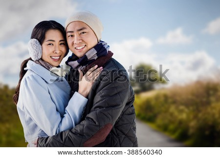 Portrait of couple embracing against country road - stock photo