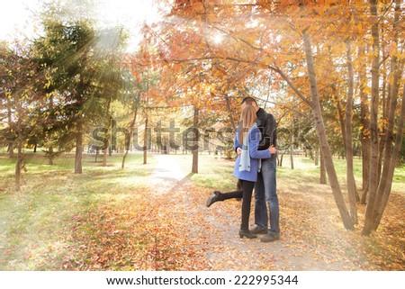 Portrait of couple enjoying kissing each other autumn fall season - stock photo