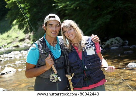 Portrait of couple fly fishing in river - stock photo