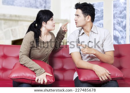 Portrait of couple having fight while sitting on sofa at home in winter day - stock photo