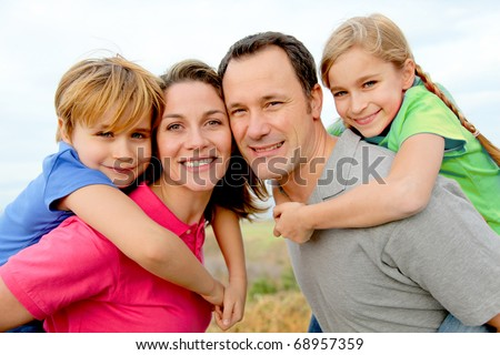 Portrait of couple holding children on their back