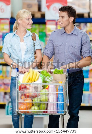 Portrait of couple in the shop with cart full of food. Concept of consumerism and healthy food